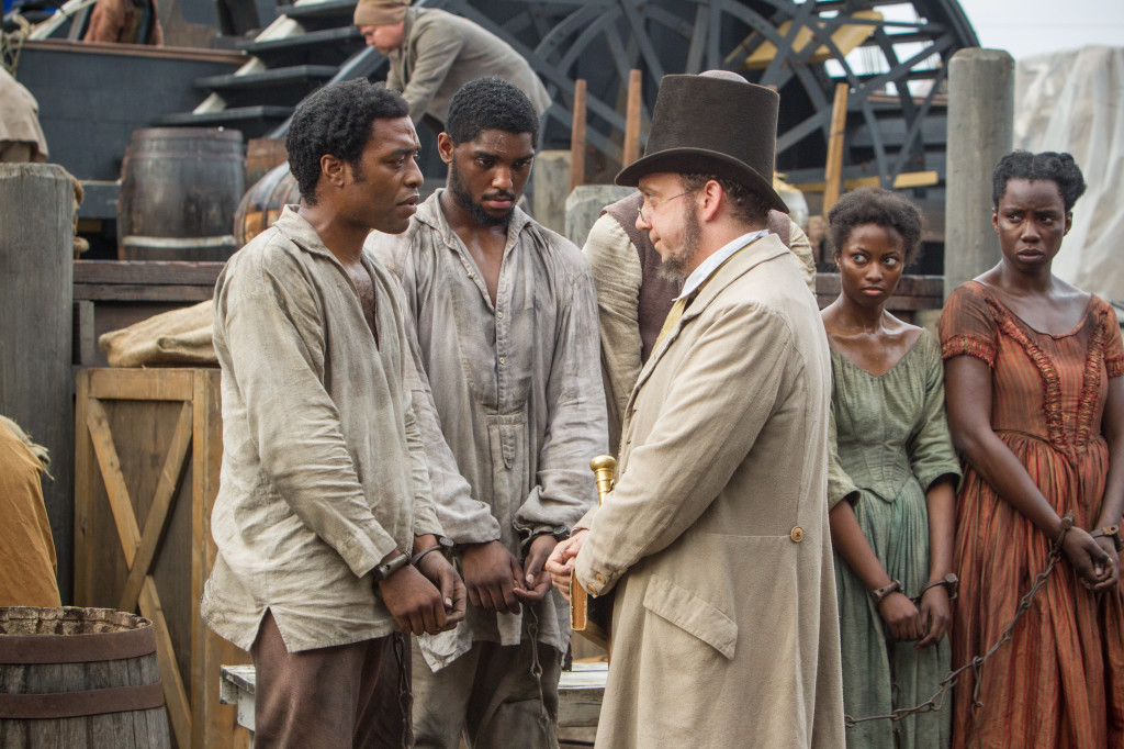Chiwetel Ejiofor (far left) as Solomon Northup and Paul Giamatti as a freeman in the 12 Years a Slave film. (Fox Searchlight)
