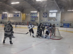 Saratoga's Jack Rittenhouse (in white, near net) just after his second period goal tied the game at 1-1.