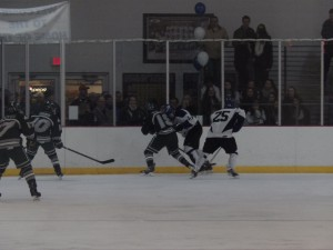 A Saratoga player skates after Shen's Zach Caswell (#18).