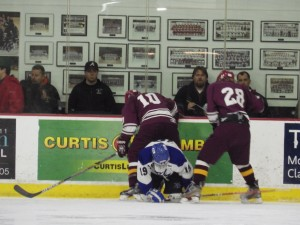 Saratoga's Jack Rittenhouse, front, fights for the puck with Burnt Hills players Ian Spack, left, and Nick Koszelak, right.