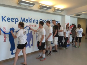 On Thursday, May 14, SADD club members cut the ribbon to officially unveil a new mural on the second floor of the high school above the main lobby. Club members designed and installed the mural to promote positive decision making among high school students. Kelsey Jackowitz for The Lightning Rod