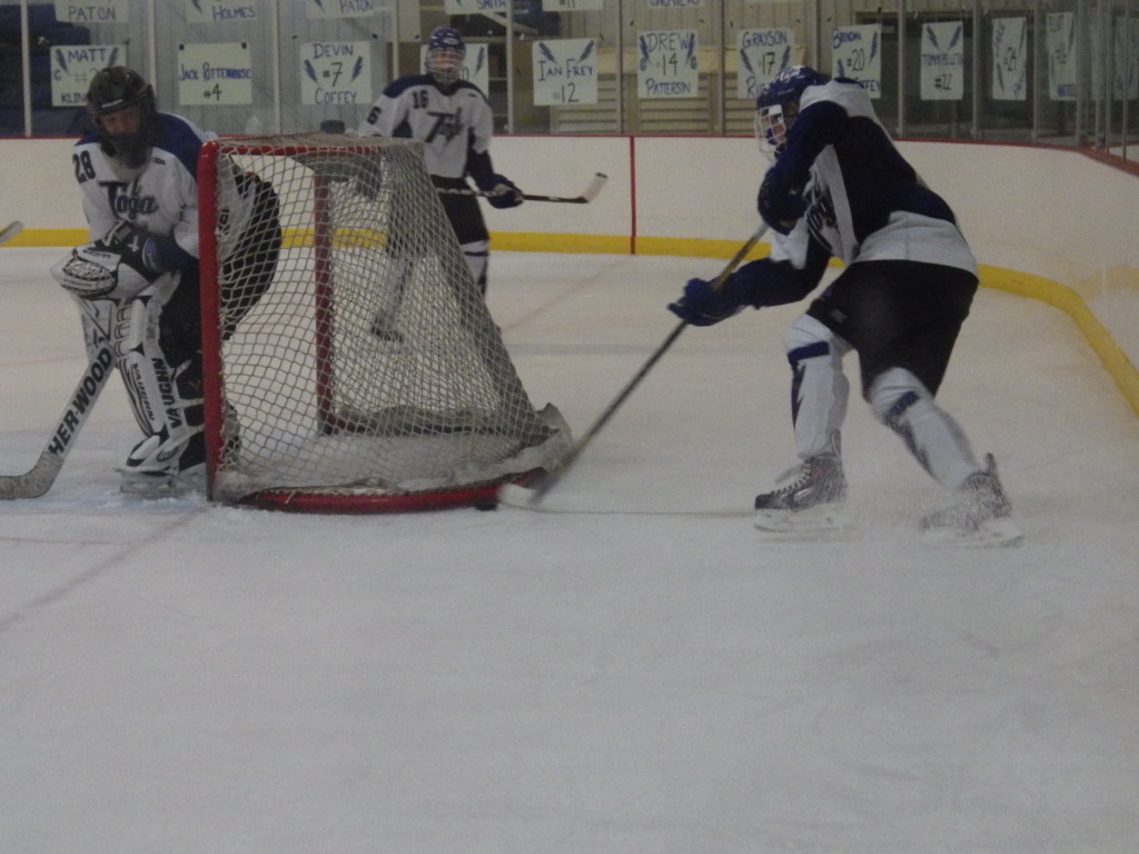 A Saratoga player clears the puck from behind the net during Friday's game as Cam McCall '15 and goalie Danny Hobbs '16 look on. The Blue Streaks defense was not at its best.