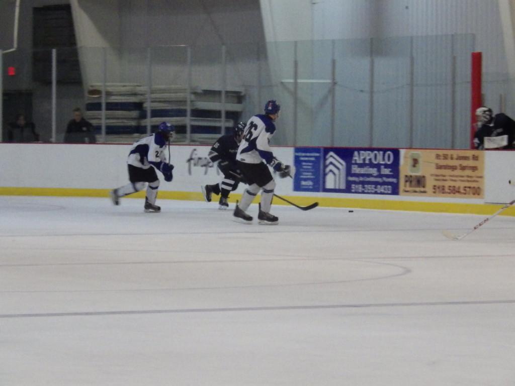 Saratoga forward Elliott Hungerford '16 skates for the puck alongside Pittsford's Bryan Cavanagh '15 during Friday's game.
