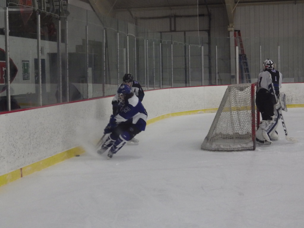 Saratoga forward JT Rafferty '15 fights for the puck with the Rivermen's Andrew Patterson '14 as GF/HF/SGF goalie Joe Lovering '14 looks on. Rafferty is the leading scorer this season for the Blue Streaks, and Lovering is the #4 goalie in Section 2, behind two of his teammates.