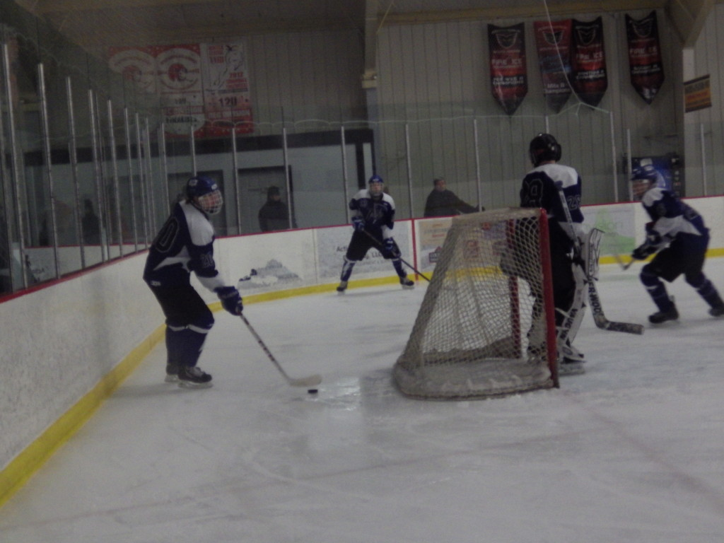 Saratoga defenseman Brendan Coffey '16 clears the puck from behind the net during Friday's game. Coach Dave Torres was happy with the Streaks' defense.