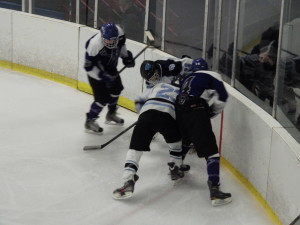 Suffern's CJ Greco '16 fights for the puck with Saratoga's Jack Rittenhouse '15.