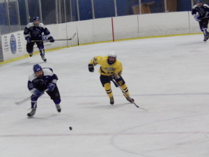 Saratoga defenseman Isaac Fisher '14 skates alongside Pelham forward Colin Raffio '14 during Saturday's game.