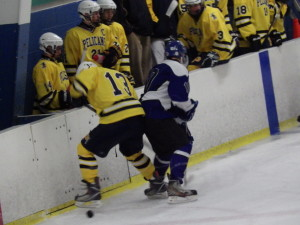 Saratoga defenseman Austin Patterson '16 fights for the puck with Pelham forward Andrew Dzenis '14.