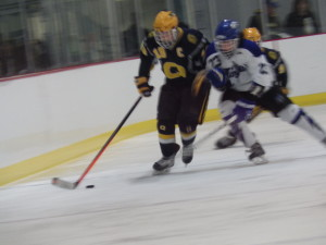 Queensbury's Michael Aarons '14 (#18) tries to get the puck from Saratoga's Zach Guzi '15.