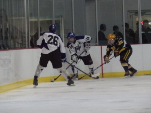 Saratoga's Drew Patterson '14 (#14) prepares to pass to Elliott Hungerford '16 as Queensbury's Ben Willows '15 attempts to intercept the puck.