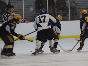 Saratoga's Grayson Rieder '14 (#17) chases the puck next to several Queensbury players.