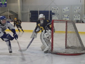 Queensbury goalie Teddy Nolan '16 readies to block a shot from behind.