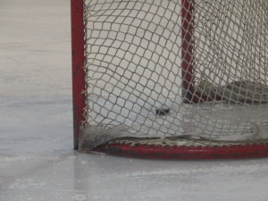 A puck sits just inside the Queensbury goal after they were taking shots during a timeout.
