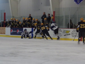 Saratoga's Cam McCall '15 (#16) loses the puck to Queensbury's Connor Tuttle '16 (#20) as Elliott Hungerford '16 (#26) comes in to help.