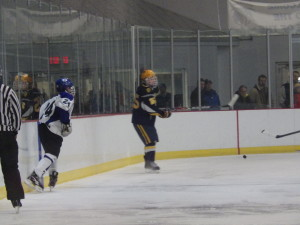 Saratoga's Jake Fauler '17 (#21) creeps up the boards towards Queensbury's Ben Willow's '15 during the third period. Fauler scored two goals during Friday's game.