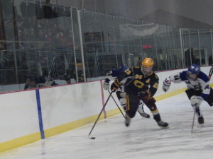 Queensbury's Shay Bendedetto '15 (#23) takes the puck into the Saratoga end during the third period, chased by Saratoga's Drew Patterson '14.
