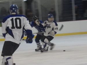 Saratoga forward Jake Fauler '17 races for the puck as defenseman Austin Patterson '16 (#10) looks on.