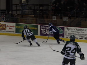 Saratoga forward Drew Patterson '14 and Shenendehowa defenseman Peter Sacks '14 race down the side of the ice as Shen forward Kyle Marr '14 looks on. Marr, the Plainsmen's leading scorer, registered one goal and two assists during the game.
