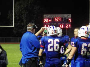 Saratoga Head Coach Terry Jones, left, talks to his players during thesecond quarter Friday.