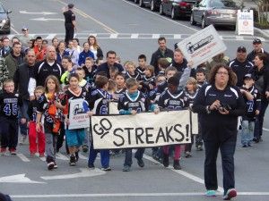 Pop Warner Football players march in the parade on Lake Avenue.