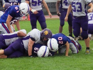 Ballston Spa's Vincent Miczek on the ground next to Saratoga's Cody Moore (#67) and Nick DeSessa (#20).