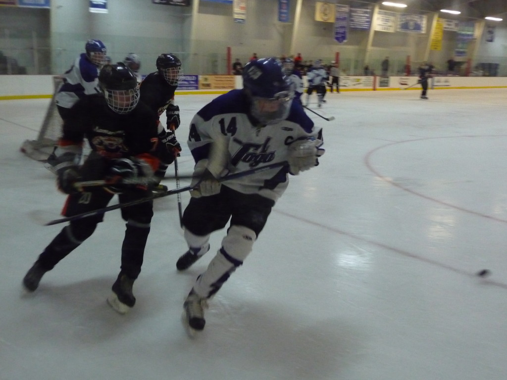 Saratoga forward and captain Drew Patterson '14 skates with  the puck during Friday's game. The Streaks won the Don Kauth Memorial Tournament played over the weekend.